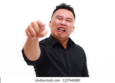 Angry furious Asian man shouting and pointing finger at camera isolated over white background