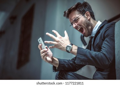 Angry, furious business man shouting at his cell phone, sitting outside a building