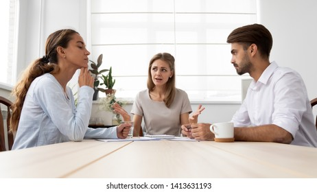 Angry furious female boss scolding diverse employees for bad work at group meeting. Ineffective incompetent workers sitting at office desk and listening with bored and annoyed expressions