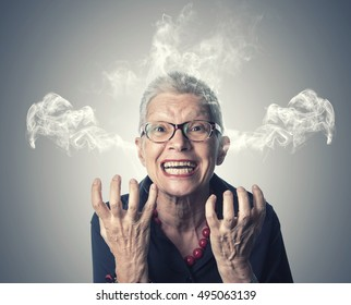 Angry and furious senior woman steaming with rage, her head is smoking