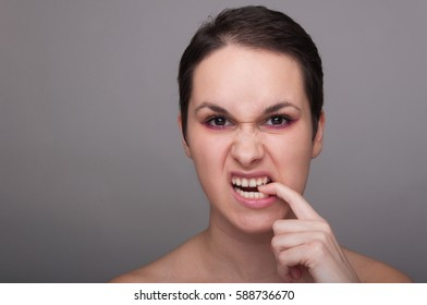 Angry or furious woman frowning and biting her finger on grey background with advertising area