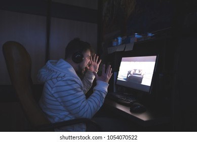 An angry gamer plays games at home on a computer. An emotional young man plays computer games and is nervous. Lose in the game