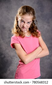 angry girl with blond hair and pink shirt in front of gray background