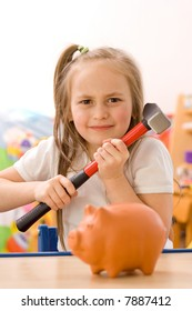 Angry girl ready to break the piggy bank with hammer [focus on the girl]