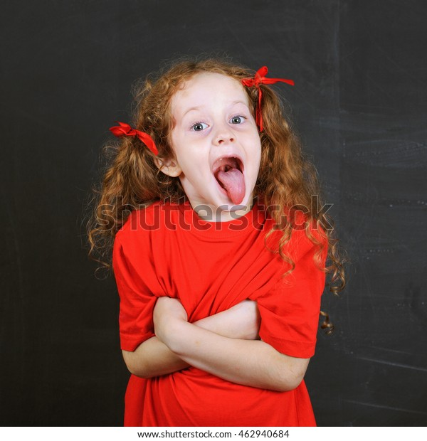 Angry girl in red t-shirt put out his tongue and  stand near blackboard. Child character. Health and medical concept.