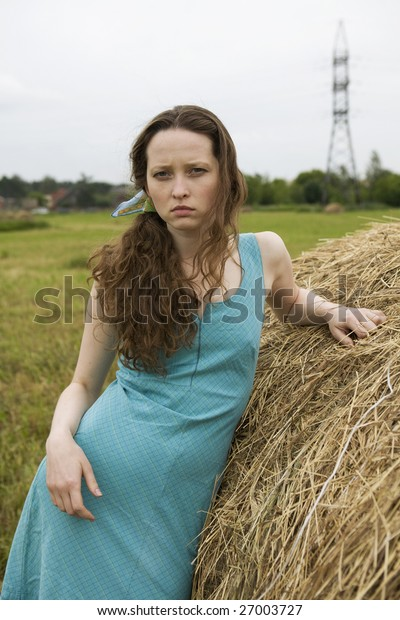angry girl standing near haystack