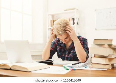 Angry girl studying at working table. Exhausted female student reading books and working on laptop. Education and technology concept