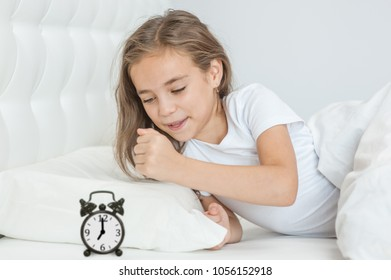 angry girl wants to break the alarm clock with her fist