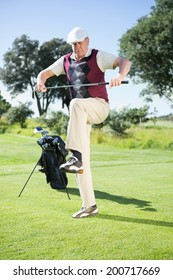 Angry golfer trying to break his club on a sunny day at the golf course