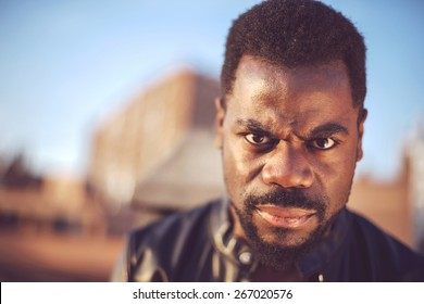 Angry good looking young black man in trendy clothes with negative space
