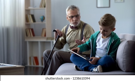 Angry grandpa scolding grandson for playing video game on tablet, generation gap