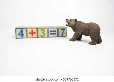 An angry grizzly bear walks towards some children's number blocks depicting a math equation. This represents the concept that schools must protect children from bears.