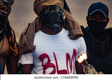 angry group of black people in gas mask riot, set fire to bottles with cloth. emotional black-skinned men can't sit at home when injustice is everywhere