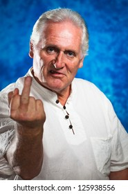 An angry grumpy mature man giving the rude middle finger and looking at camera.