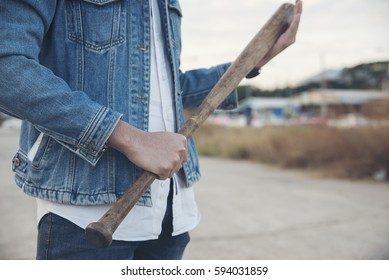 Angry guy (criminal) holding baseball bat.Closed up of hand's violence man wearing blue jeans and jacket standing on the cement patio.