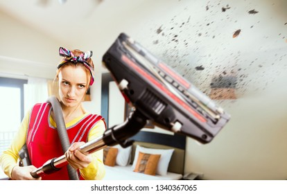 Angry housewife in apron with vacuum cleaner