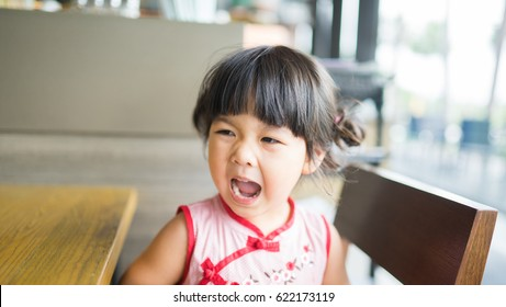 angry and hungry little asian girl is screaming in restaurant.angry kid.Facial expression.