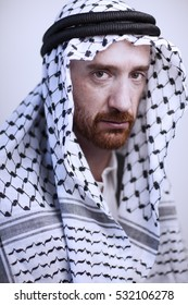 Angry and intense Arab man with a red beard wearing a black and white Muslim head wrap