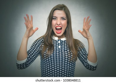 Angry irritated woman is shouting isolated on gray background. Debates. Quarrel. Demanding dissatisfied boss.