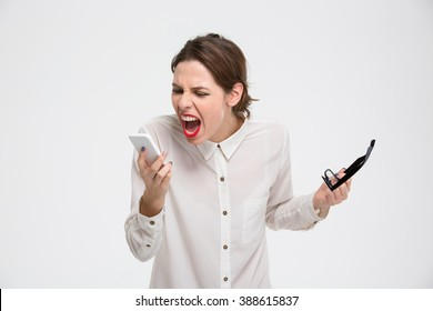 Angry irritated young business woman holding mobile phone and glases and shouting over white background
