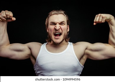 angry jock showing his musculars isolated on the black background. rage concept. violent sport