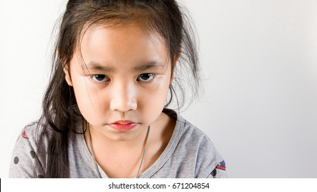 Angry little Asia kid or Stubborn Student Over Grey background.Facial Expression.Stubborn,Sad,Upset Little girl and child Concept