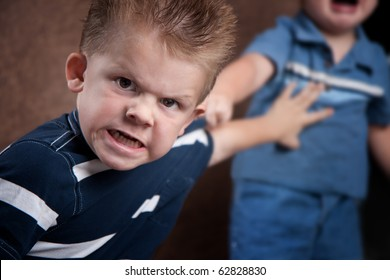Angry little boy glaring at the camera, fighting with his brother who is screaming