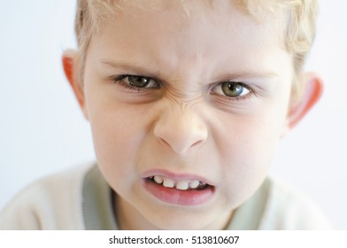 Angry little boy looks straight to camera