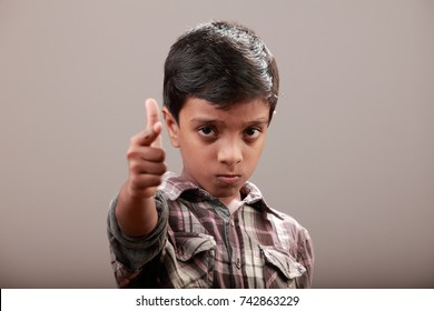 Angry little boy points his index finger