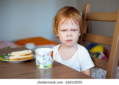 An angry little boy and a sandwich with butter.