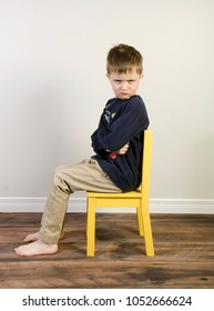 An angry little boy sits on a yellow time out chair on a wooden floor