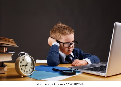Angry little boy works with a laptop at the table in school