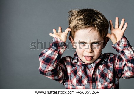 angry little brat enjoying making a grimace, sticking out his tongue, playing with his hands for  misbehavior, contrast effects, grey background