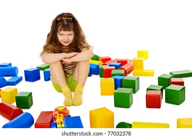 Angry little girl among the scattered toys isolated on white background