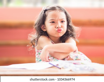 Angry little girl with cross one's arm.The emotion of a child when her mother forbids watching cartoons and tell her to draw.