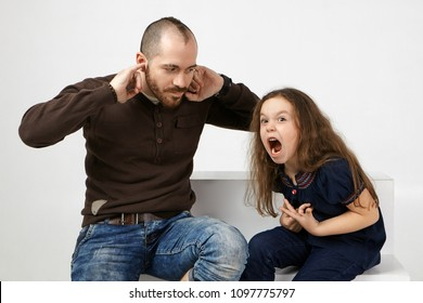 Angry little girl with long loose hair shouting, misbehaving because father didn't allow her watching cartoons. Frustrated young bearded man plugging ears, can't stand annoying screams by his daughter