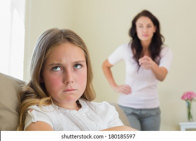 Angry little girl with mother scolding her in background at home