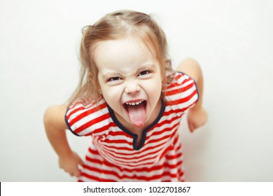 Angry little girl shows her tongue in funny grimace