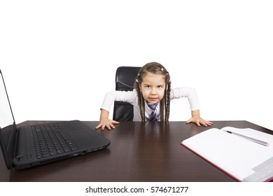Angry little girl  sitting at the table. Business concept