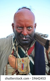 Angry looking warrior dressed in war paint and wearing jewelry