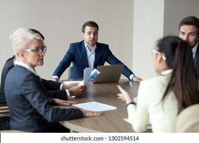 Angry mad boss executive manager shouting having conflict disagreement with employee at group office meeting scolding criticizing worker for business problem failure bad work at team staff briefing