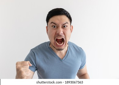 Angry and mad face of Asian man in blue t-shirt on isolated background.
