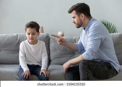 Angry mad father scolding lecturing sad preschool kid son for bad behavior at home, serious parent dad punish little upset guilty child boy pointing finger demand discipline, family conflicts concept