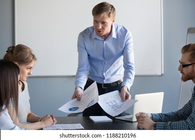 Angry mad male boss executive architect or designer shouting reprimanding scolding stressed team of incompetent employees for bad project result, mistakes in work or money loss at group meeting