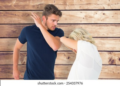 Angry man about to hit his girlfriend against wooden planks background