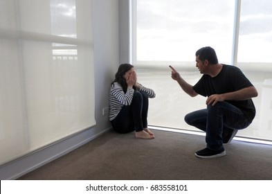 Angry man (age 40-45) telling off a crying woman (age 30-35) sitting in the corner on the floor. Family life concept. Real people. Copy space