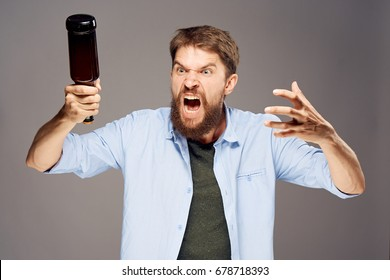 Angry man with a bottle of beer on a light background