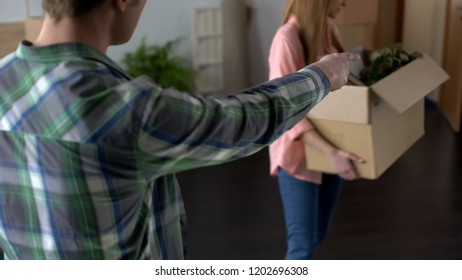 Angry man breaking up with girlfriend, unhappy woman leaving house, stuff in box