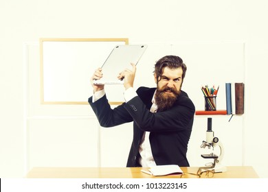 Angry man businessman male scientist hipster smashes laptop furiously in office with board for copy space on white background