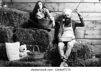 Angry man chef cook or baker with beard and moustache in hat toque and cute girl cookee teenager in apron sit on straw bales on rustic background.